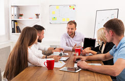 Business meeting. Young hipsters businessmen and women at modern office Royalty Free Stock Photos