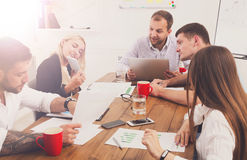 Business meeting. Young hipsters businessmen and women at modern office. Business meeting. Young happy businessmen and women at modern office, team corporate Royalty Free Stock Photos