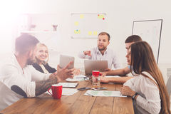 Business meeting. Young hipsters businessmen and women at modern office. Business meeting. Young happy businessmen and women at modern office, team discussion at Stock Image