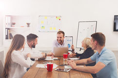 Business meeting. Young hipsters businessmen and women at modern office. Business meeting. Young happy businessmen and women at modern office, team friendly Royalty Free Stock Photo