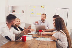 Business meeting. Young hipsters businessmen and women at modern office. Team discussion at workplace, show information on tablet. Brainstorming and Royalty Free Stock Photography