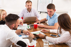 Business meeting. Young hipsters businessmen and women at modern office. Team discussion at workplace, show information on tablet. Brainstorming and Stock Images