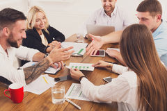 Business meeting. Young hipsters businessmen and women at modern office. Team vivid discussion at workplace. Brainstorming and communication with partners for Royalty Free Stock Photos