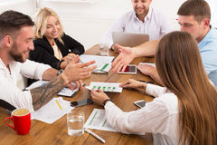 Business meeting. Young hipsters businessmen and women at modern office. Team vivid discussion at workplace. Brainstorming and communication with partners for Royalty Free Stock Photo