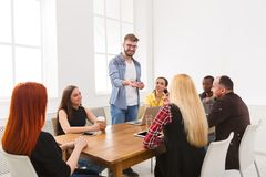Business meeting. Young team in modern office. Business corporate meeting of multiethnic team. Office discussion, communication with partners, one men is making royalty free stock photos