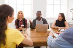 Business meeting. Young team in modern office. Business corporate meeting of multiethnic team. Office discussion, communication with partners, copy space royalty free stock image