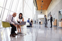 Business Meetings In Busy Office Foyer Area Stock Photos