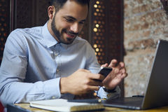 Business men in blue shirt using smartphone connected to wireless internet in cafe Stock Image