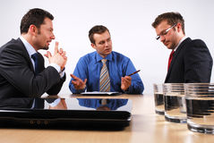 Business men coaching. Three businessmen sitting at a table negotiating a contract royalty free stock photos