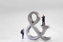 Business men figurines next Ampersand sign Royalty Free Stock Photo