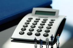 Business men figurines standing in front of calculator, rear vie Stock Images