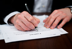 Business men filling out contract on table. Stock Image