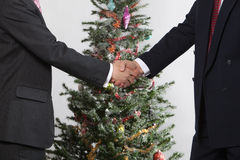 Business men in front christmas tree Royalty Free Stock Photography