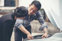 Business men help business women check and repair broken cars royalty free stock images