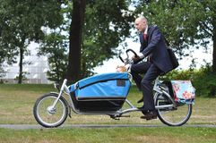 Business men hurrying to the child�s creche. Business men hurrying on the carriere bike to the child creche royalty free stock photography