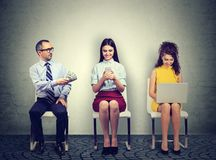Mature business man offering money to a young woman using mobile phone sitting next to an employee working on laptop computer Stock Photo
