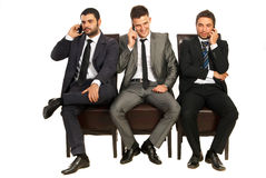Business men on the phones. Three business men sitting on chairs in a line and speaking by phones mobile isolated on white background Stock Images