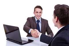 Business men reaching to an agreement. Young business men reaching to an agreement at their desk, against white background Royalty Free Stock Photo