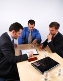 Business men reading a contract. Three businessmen sitting at a table negotiating and reading a contract royalty free stock photo