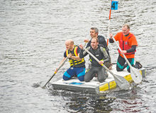Business men row down the river Ness. Royalty Free Stock Photo
