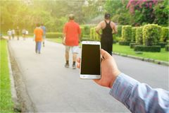 Business Men`s hands holding the mobile phone on public park. Blur background Stock Images
