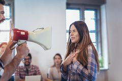 Business men screaming in megaphones at sad depressed young woman royalty free stock photography