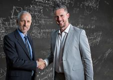 Business men shaking hands against grey wall with math doodles. Digital composite of Business men shaking hands against grey wall with math doodles Royalty Free Stock Photo