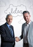 Business men shaking hands against white wall with idea doodles Royalty Free Stock Photo