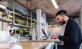 Business man sitting at restaurant working on laptop. Business men sitting at restaurant working on laptop. Caucasian businessman at restaurant using laptop Royalty Free Stock Photo
