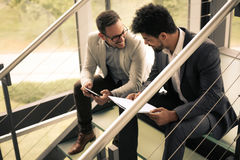 Business men sitting on the stairs. Business people having conversation on stairs of business building Royalty Free Stock Image