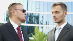 Business men standing next to an office building stock footage