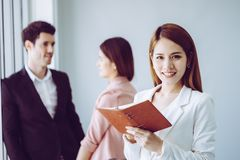 Business man taking note in front of two friend office worker in the background. for woman confidence concept. Business men is taking note in front of two friend stock photos