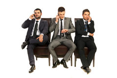 Business men talking by phones. Business men sitting on chairs in a line and having conversation isolated on white background Stock Images