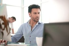 Business man talking to a colleague sitting at his Desk stock images
