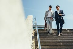 Business men talking and walking down the steps royalty free stock image