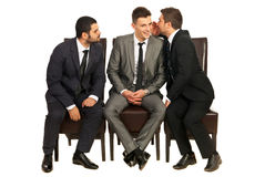 Business men telling a secret. To a colleague while other trying to listen and sitting all on chiars isolated on white background stock image