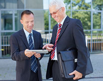 Business men using a tablet. Two happy business men using a tablet computer outside the office Royalty Free Stock Photography