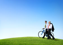 Business Men Walking Through the Field with a Bicycle.  Royalty Free Stock Images