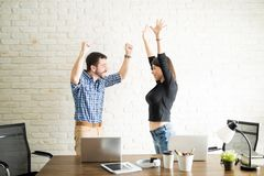 Work partners celebrating good news. Business men and women celebrating some good news with their hands in the air Royalty Free Stock Image