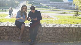 Business men and women use a tablet and a phone in the park. Shot in 4k stock video footage