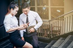Business man and woman Using smartphone standing talking and vie Royalty Free Stock Photo