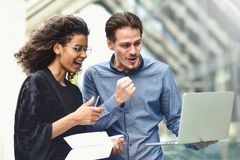 Business meeting. Man and woman discussing work and looking at the laptop screen. Working together in the open air. royalty free stock photography