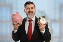 Business Metaphor of Time is Money. Hispanic senior businessman holding piggy bank and clock to represent Time is Money metaphor Stock Photos