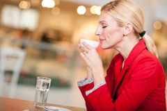 Business middle-aged woman enjoying coffee in a cafe bar Stock Images