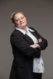 Business middle-aged woman with glasses in black suit. On a gray background Royalty Free Stock Photography