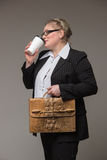 Business middle-aged woman with glasses and leather briefcase an. Business middle-aged woman with glasses carrying a briefcase and documents drinking coffee Royalty Free Stock Photo