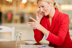 Business middle-aged woman using a mobile phone in coffee shop Stock Photo