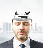 Business mindset concept. Portrait of handsome caucasian businessman with closed eyes and abstract relaxing person miniature inside head on city background royalty free stock photo
