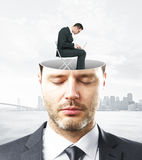 Business mindset concept. Portrait of handsome caucasian businessman with closed eyes and abstract working person miniature inside head on city background stock photos