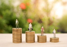 Business miniature people and money stack gold coin Stock Photo